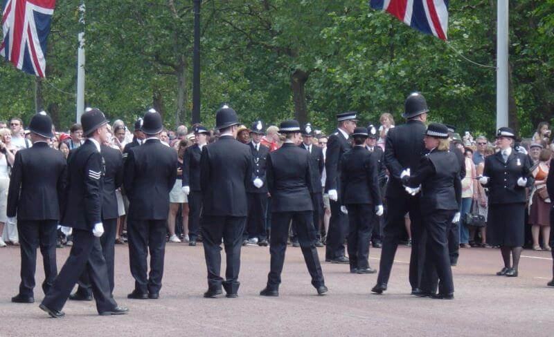 police officers leading tourists to Buckingham Palace