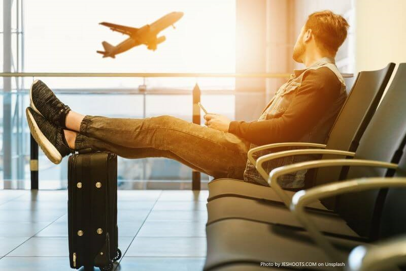 a man sitting chair and looking at an airplane